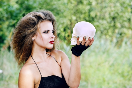 Beautiful witch holding a human skull. halloween concept