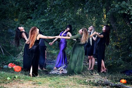 jóvenes hermosas brujas bailando en las manos sosteniendo forestales