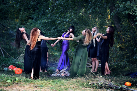 sabbath: young beautiful witches dancing in the forest holding hands