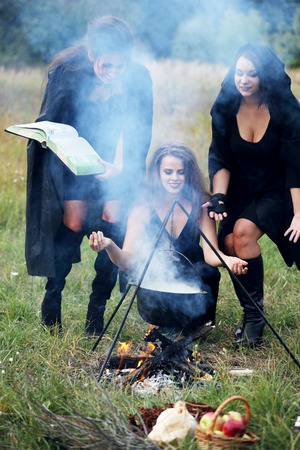three witches conjure with potion, in the forest Stock Photo