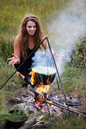 mystic place: Witch preparing a potion in the meadow Stock Photo