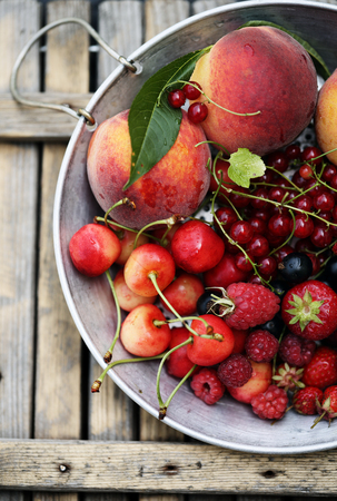 garden organic berries and fruits on a sieve Stock Photo