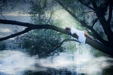 Mooie vrouw in witte kleding die op een boom over de rivier Stockfoto