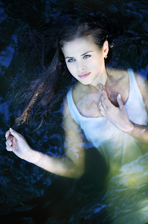 adult mermaid: Young beautiful girl in a dark river water, top view