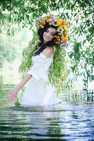 Beautiful girl in a wreath splashing in water
