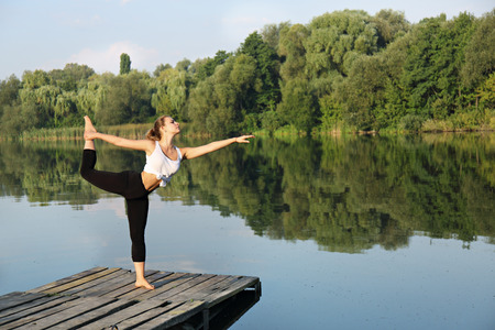 Young beautiful woman engaged in yoga on the river bank, Asana on balance Nataraja asana