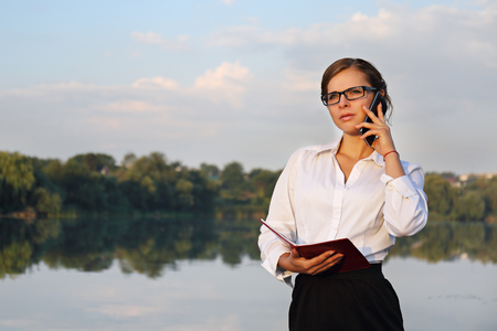 illustrating: Concept illustrating remote work,Business woman speaks on the phone on the beach