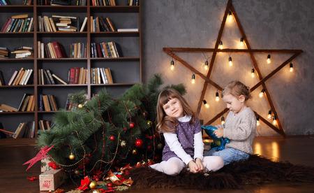 Children near a fallen Christmas tree. Christmas concept