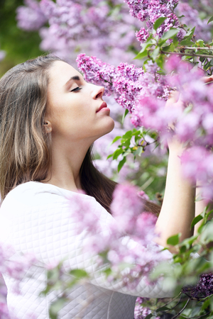 beautiful Girl smelling a lilac Stock Photo