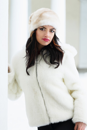 Beautiful woman in a white fur coat and hat in winter