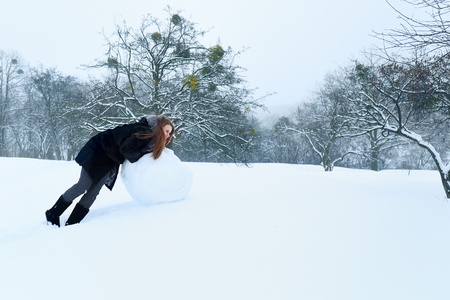 Woman with big heavy snow ball