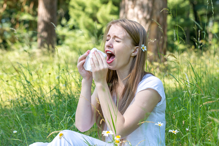 Woman sneezing in the woods
