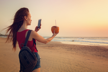 A woman is taking pictures of a coconut