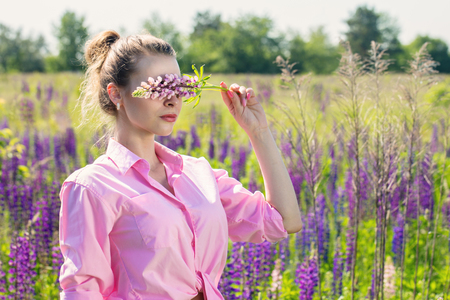 Woman covered her eyes with a flower Banque d'images