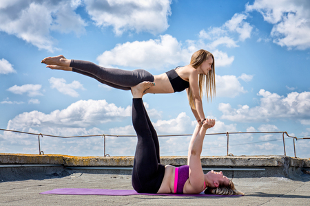 Two girls are engaged in acro yoga