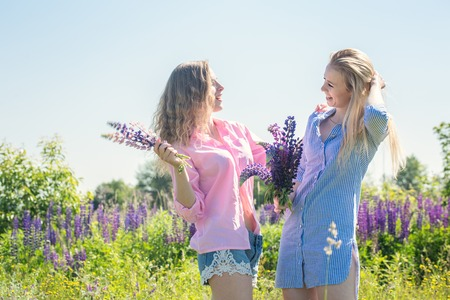 Two cheerful friends on the field with lupines