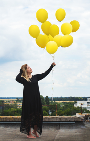 A woman with a big bunch of balloons