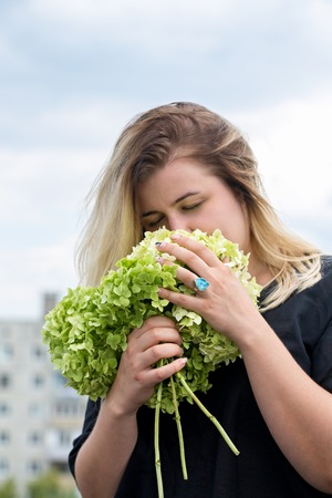 woman sniffing a bouquet of hydrangeas Stock Photo