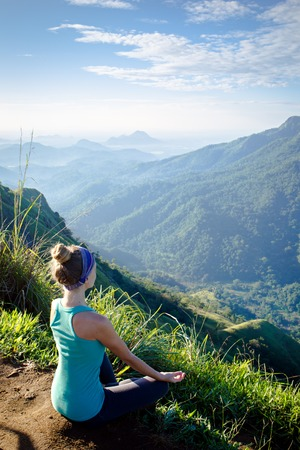 Young woman meditating on top of a mountain