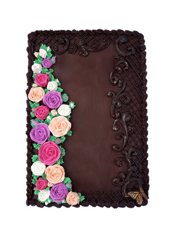 A large chocolate cake in the shape of a book with colorful flowers from cream