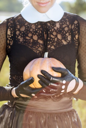 Hands in gloves hold a pumpkin Stok Fotoğraf