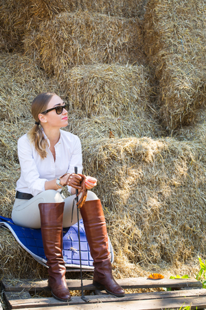 woman in a horse riding costume resting in the hayloft