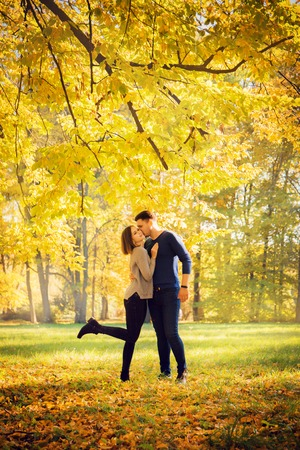 couple kissing under an autumn tree