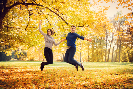 couple jumping under an autumn tree