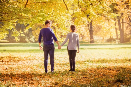 Young couple walking in park Stockfoto