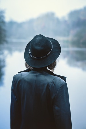 The girl in the hat looks at the river