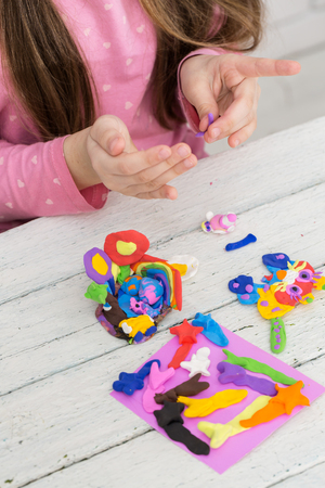 girl sculpts a figure of plasticine Imagens