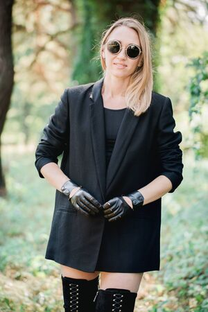 Beautiful blonde in a black jacket and gloves handmade with a chain
