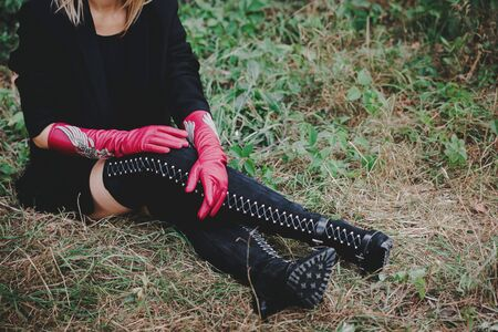 Woman in high boots lace-up and long red gloves sitting on the grass