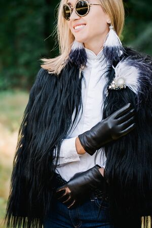 Beautiful stylish blonde in leather gloves and a fur jacket