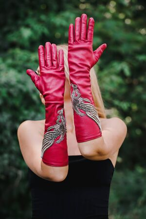 Beautiful stylish blonde in long red gloves with embroidery