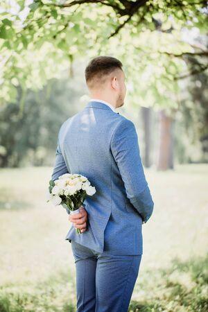 Novio con un ramo de flores en sus manos esperando a la novia en el parque Foto de archivo