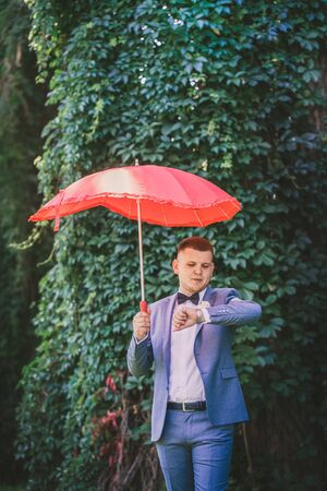Man in a suit with a red umbrella looks at the clock