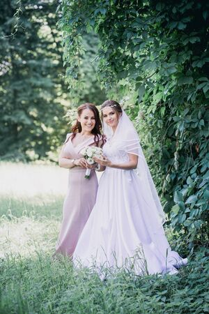 Bride and bridesmaid on a green background in the park