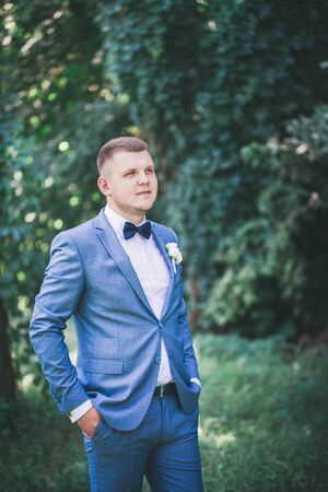 Handsome groom in suit and bow-tie in the park 版權商用圖片