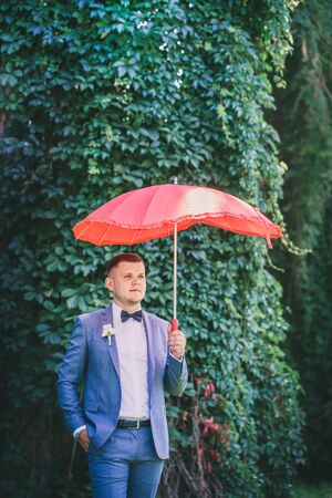 Man in a suit with a red umbrella in the park 版權商用圖片