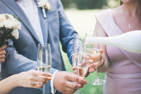 newlyweds with guests drink champagne in the park Фото со стока