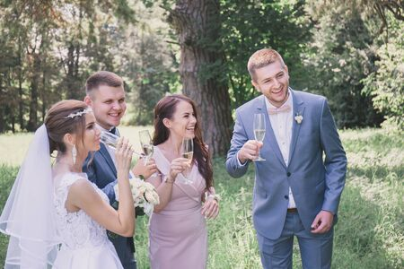 newlyweds with guests drink champagne in the park Foto de archivo