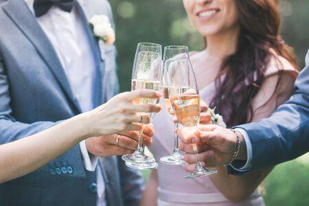 Recién casados con invitados beben champán en el parque