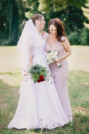 Beautiful girls Bride and bridesmaid with bouquets in the park