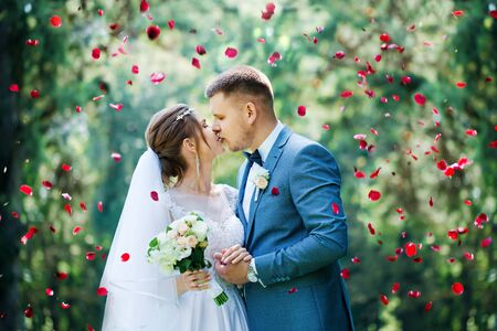 Portrait of the bride and groom with a bouquet of flowers in the park
