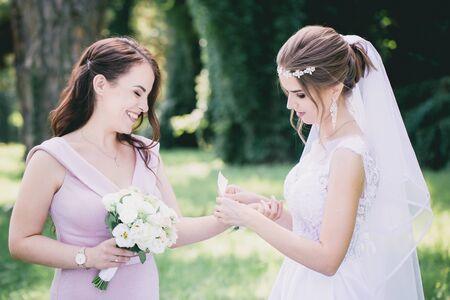 Panna młoda przywiązuje ślubną bransoletkę do swojej druhny Zdjęcie Seryjne