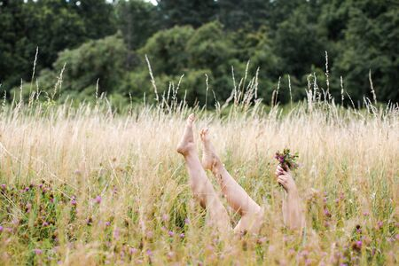 Female legs and hands with a bouquet of clover protrude from the grass in the meadow Stock Photo