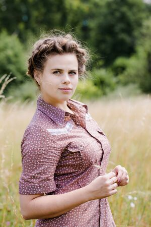 Young beautiful brunette with braid on her head in a country style dress on the field