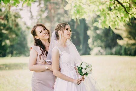 Schöne Mädchen Braut und Brautjungfer mit einem Blumenstrauß im Park