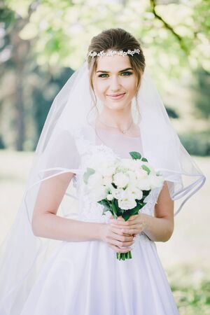 Portrait of a beautiful bride in veil with a bouquet of flowers in the park